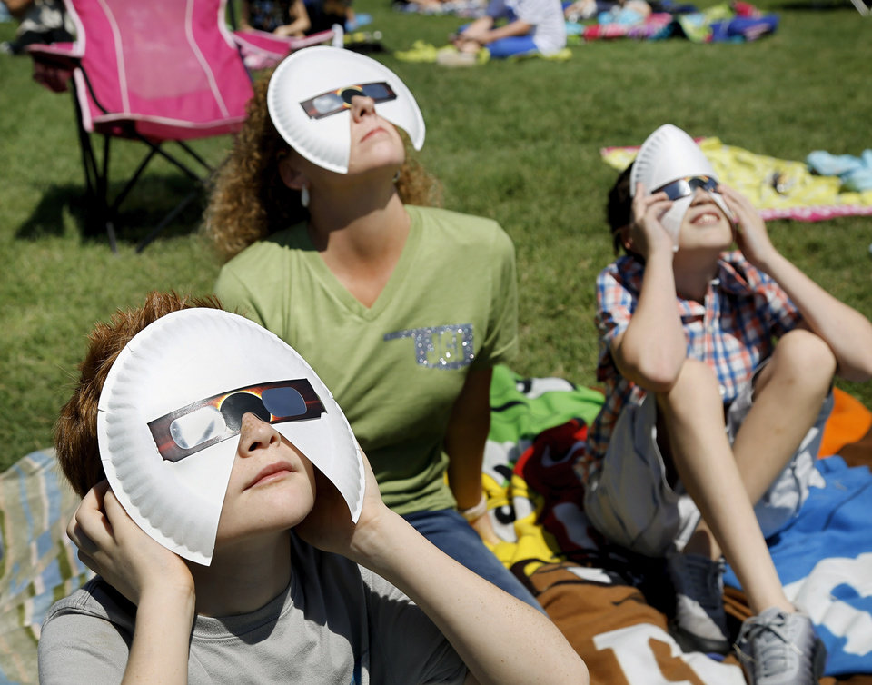 Photo - Students Willy Brandt, left, and Paden Eastep, sit with teacher assistant Tassie Burke and use modified viewing glasses to watch the eclipse. The entire student body, faculty and some parents gathered in a field on the north side of  James Griffith Intermediate School to view the solar eclipse Monday afternoon, Aug. 21, 2017.  Special glasses with very dark lenses were purchased to allow teachers and students to safely view the celestial event. Children were served  Moon Pies as a snack to enjoy while viewing the eclipse. Photo by Jim Beckel, The Oklahoman