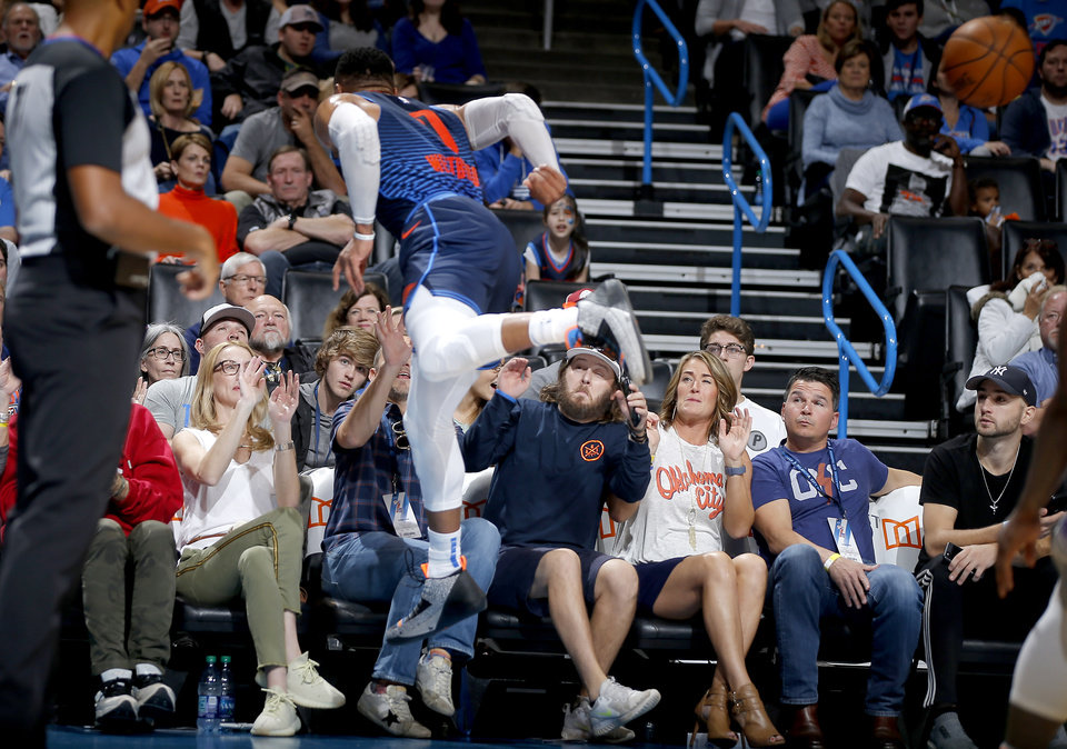 Photo - Oklahoma City's Russell Westbrook (0) goes into the crowd after chasing the ball during an NBA basketball game between the Oklahoma City Thunder and the Sacramento Kings at Chesapeake Energy Arena in Oklahoma City, Sunday, Oct. 21, 2018. Photo by Bryan Terry, The Oklahoman