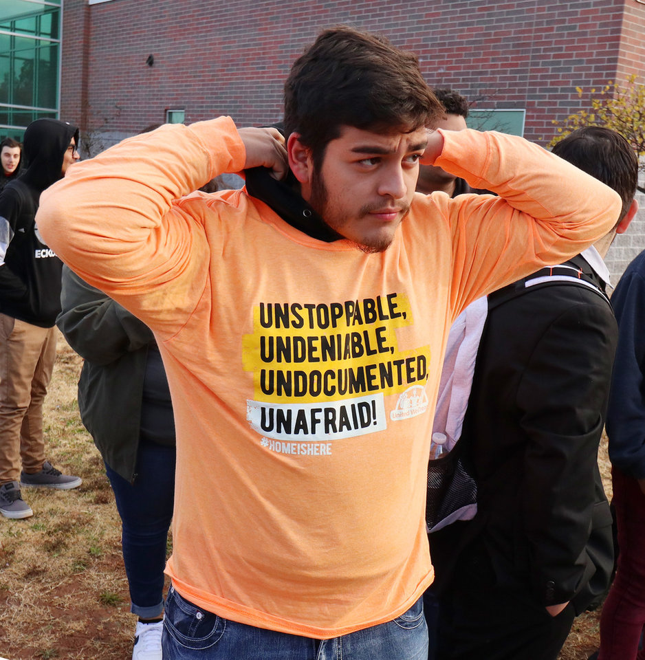 "Photo - Senior Carlos Gonzalez puts on a ""Unstopable. Undeniable. Undocumented. Unafraid! #HomeIsHere"" tee shirt at the DACA support rally at U.S. Grant High School Friday, November 8, 2019. Photo by Doug Hoke"