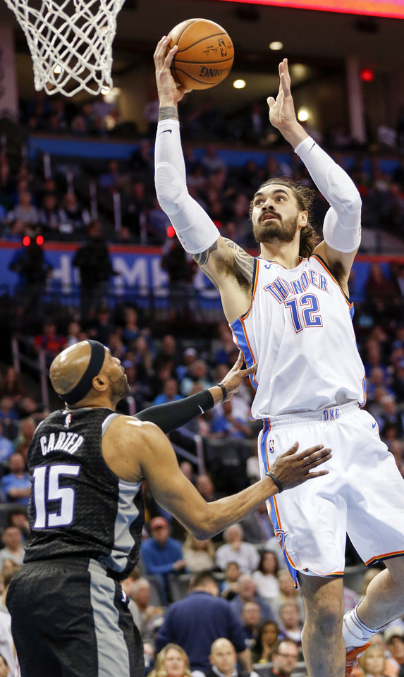 Photo - Oklahoma City's Steven Adams (12) takes the ball to the basket against Sacramento's Vince Carter (15) during an NBA basketball game between the Oklahoma City Thunder and the Sacramento Kings at Chesapeake Energy Arena in Oklahoma City, Monday, March 12, 2018. Photo by Nate Billings, The Oklahoman