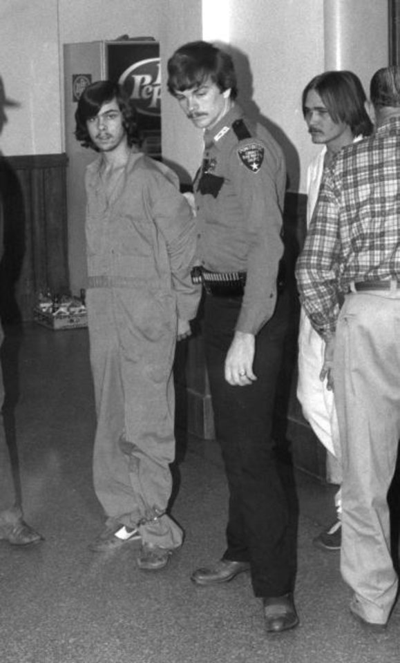 Photo -  Karl Allen Fontenot, left, and Tommy Jesse Ward, extreme right, were led through the courthouse during their preliminary hearing on Jan. 15, 1985, in McAlester. [THE OKLAHOMAN ARCHIVES]