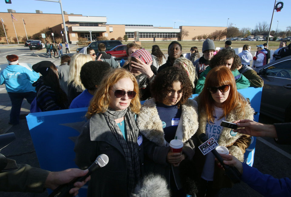 Photo - Danielle Brown, middle, a sophomore at Norman High School, speaks to the media with her aunt Stacey Wright, left, and her mother, Kim Wright, before a student-planned walkout to protest bullying and the treatment of sexual assault victims at Norman High School in Norman, OK, Monday, November 24, 2014,  Photo by Paul Hellstern, The Oklahoman