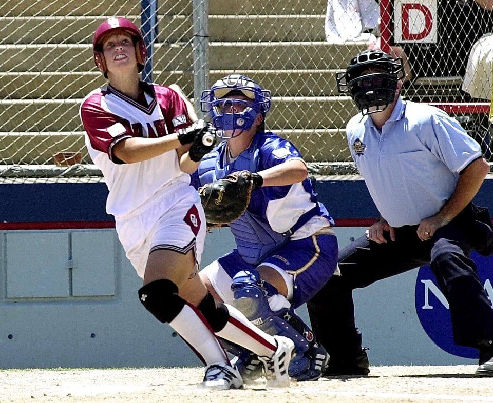 Photo - NCAA SOFTBALL WOMEN'S COLLEGE WORLD SERIES CHAMPIONSHIP: OKLAHOMA SOONERS #23 LISA CAREY WATCHES HER BALL LEAVE THE PARK IN MONDAY AFTERNOONS COLLEGE WORLD SERIES AGAISNT UCLA. LISA HIT THIS  2 RUN HOMER IN THE TOP OF THE 3RD INNING. UCLA CATCHER AMANDA FREED LOOKS ON.