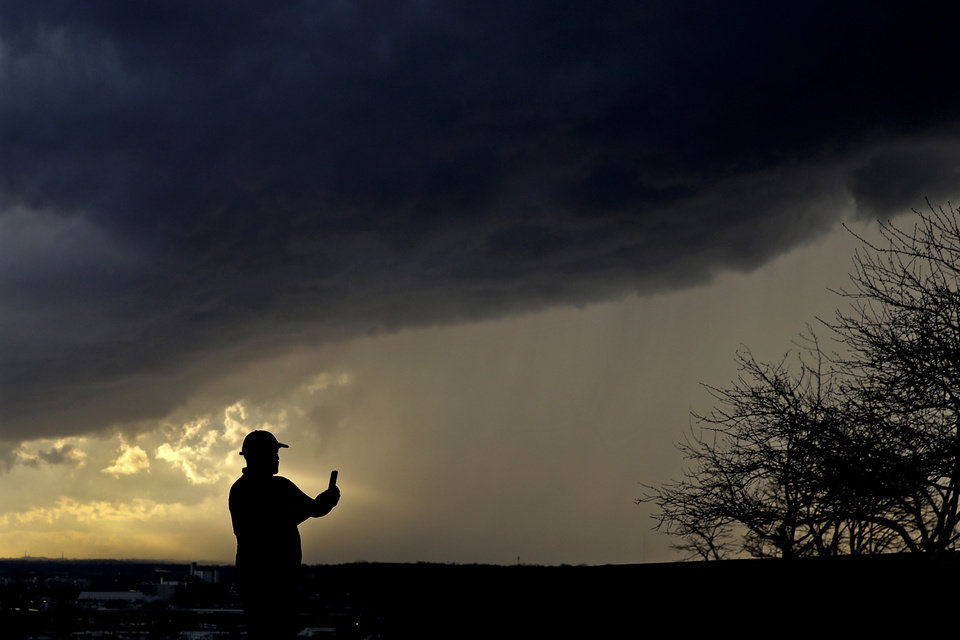 Photo -  In this March 19, 2020, photo, a man looks at his phone storm clouds pass overhead from the Liberty Memorial in Kansas City, Mo. The coronavirus pandemic is leading to information overload for many people, often making it difficult to separate fact from fiction and rumor from deliberate efforts to mislead. (AP Photo/Charlie Riedel)