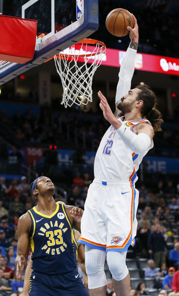 Photo - Oklahoma City's Steven Adams (12) dunks the ball next to Indiana's Myles Turner (33) in the first quarter during an NBA basketball game between the Indiana Pacers and the Oklahoma City Thunder at Chesapeake Energy Arena in Oklahoma City, Wednesday, Dec. 4, 2019. [Nate Billings/The Oklahoman]