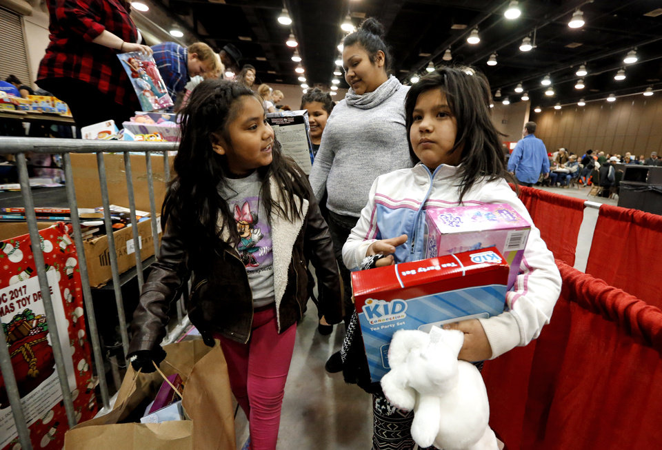 Photo - Sisters Maria and Joanna Florez carry their presents after eating during the annual Red Andrews Christmas Dinner in the Cox Convention Center on Monday, Dec. 25, 2017 in Oklahoma City, Okla.  Photo by Steve Sisney, The Oklahoman