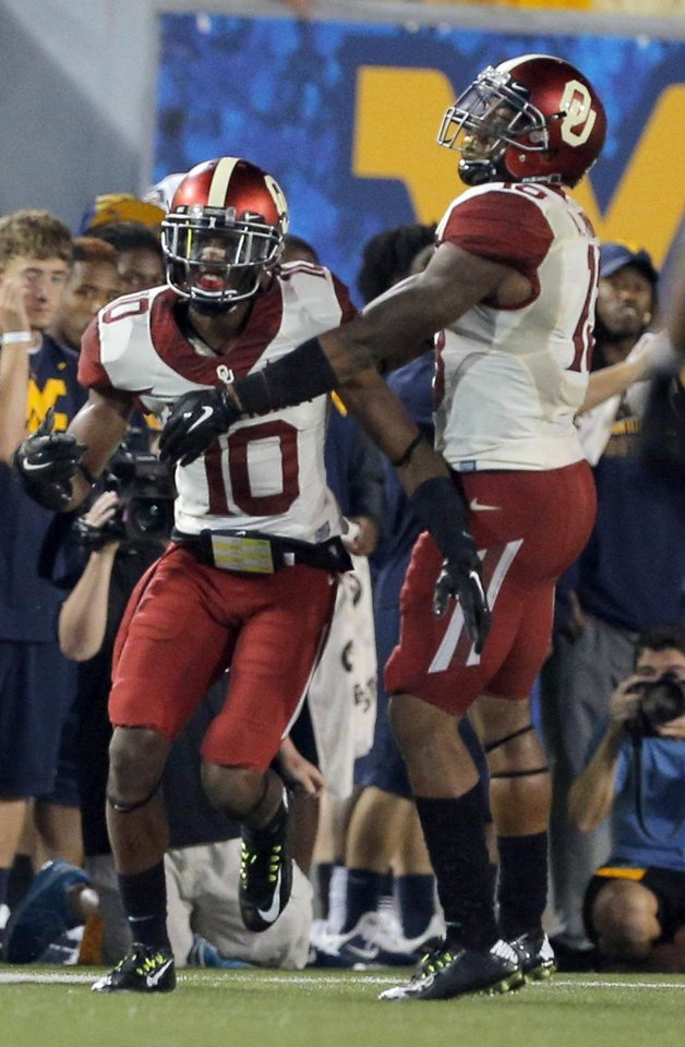 Photo - Oklahoma's Quentin Hayes (10) and Ahmad Thomas (13) celebrate a Hayes interception during the college football game between West Virginia  Mountaineers and the University of Oklahoma Sooners at Milan Puskar Stadium in Morgantown, W.Va., Saturday, Sept. 20, 2014. Photo by Sarah Phipps, The Oklahoman