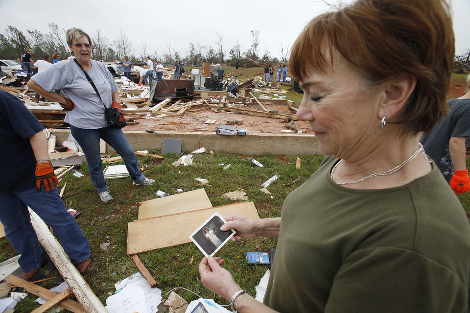 Photo - Administrative assistant LaDonna Cockerham looks at one of her wedding photos, that had been in her desk, that was found in the debris of her office at the Little Axe School Central Office, Tuesday, May 11, 2010. The school was hit by a tornado Monday, May 10, 2010. Photo by David McDaniel, The Oklahoman