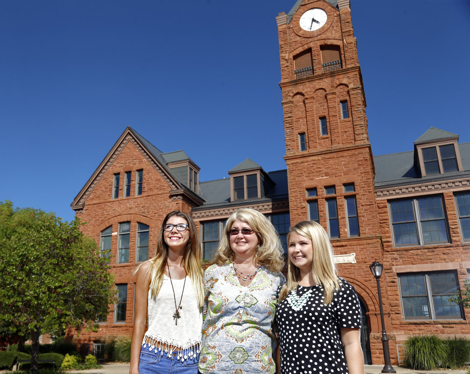 Photo -  Julie Robinson stands between daughters Sesily Monday, left, and Sydney Monday on the University of Central Oklahoma campus in Edmond. The sisters both attend UCO, one on a scholarship and one with the aid of student loans. Robinson and her husband also have two younger children to put through college. Photo by Sarah Phipps, The Oklahoman   SARAH PHIPPS -
