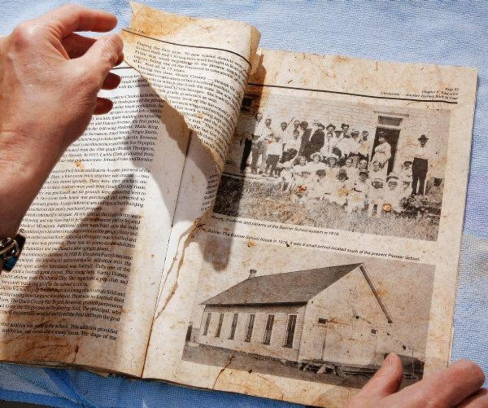 Photo - Sheila Rose found this wet and dirty book in her back yard Tuesday evening while cleaning up storm debris at her Midwest City home. The old book is about the early history of Chickasha.  JIM BECKEL - THE OKLAHOMAN