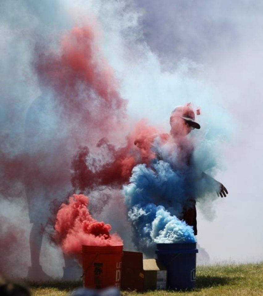 Photo -  Juan Lechuga stands in red, white and blue smoke during a watch party at Together Square. [Nate Billings/The Oklahoman]