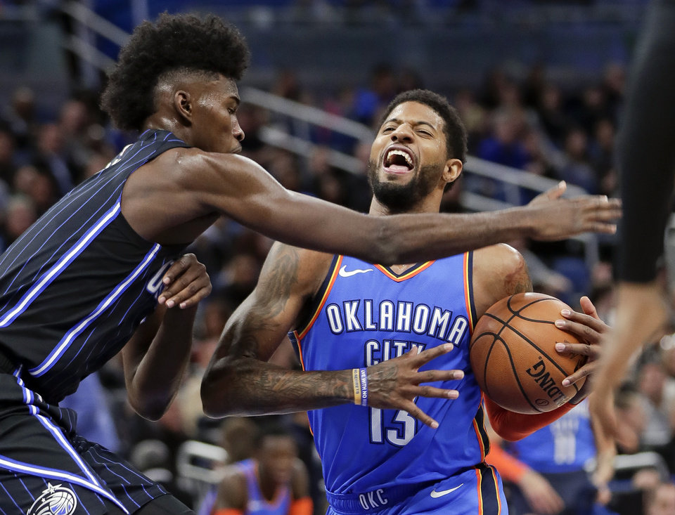 Photo - Oklahoma City Thunder's Paul George, right, goes to the basket against Orlando Magic's Jonathan Isaac, left, during the first half of an NBA basketball game, Tuesday, Jan. 29, 2019, in Orlando, Fla. (AP Photo/John Raoux)