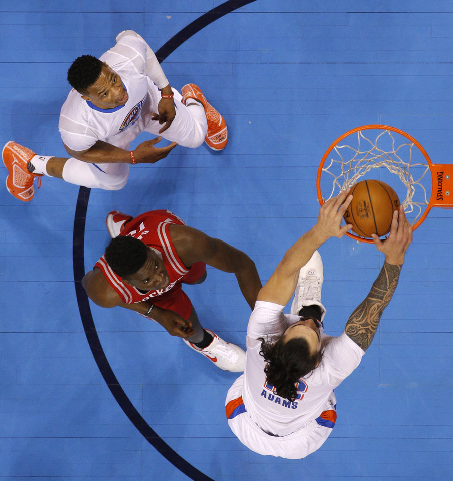 Photo - Oklahoma City's Steven Adams (12) dunks beside Houston's Clint Capela (15) as Russell Westbrook (0) watches during an NBA basketball game between the Oklahoma City Thunder and the Houston Rockets at Chesapeake Energy Arena in Oklahoma City, Tuesday, March 22, 2016. Photo by Bryan Terry, The Oklahoman