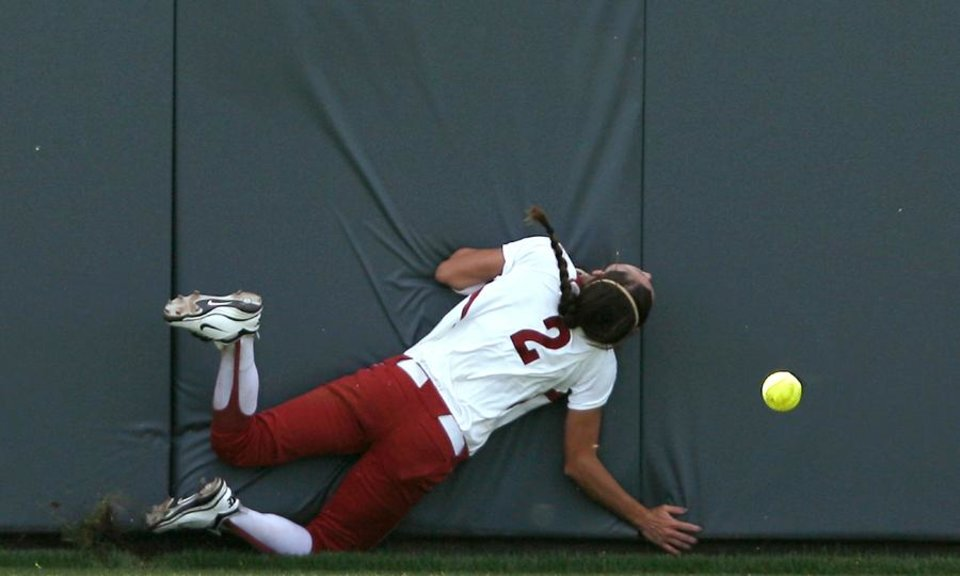 Photo -  TU / COLLEGE SOFTBALL: Oklahoma's Brianna Turang hits the wall as she chases a ball in the outfield during the Sooners' game against Tulsa during the NCAA Softball Regional at the OU Softball Complex on the University of Oklahoma campus in Norman, Okla., on Sunday, May 22, 2011. The Sooners lost the first game to the Golden Hurricane 4-3 in 9 innings. Photo by John Clanton, The Oklahoman ORG XMIT: KOD