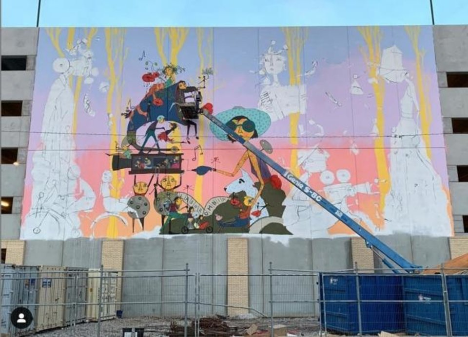 Photo -  Denise Duong works in March on one of two towering murals on the West Village Parking Garage, 927 W Sheridan Ave. [Photo provided]