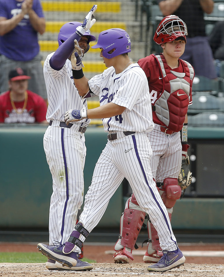 Photo - Oklahoma's Brady Lindsly watches as TCU's Johnny Rizer (4) and Austin Henry (3) celebrate after Rizer scored in the fourth inning of a Big 12 baseball tournament game between the University of Oklahoma (OU) and TCU at Chickasaw Bricktown Ballpark in Oklahoma City, Okla., Thursday, May 23, 2019.  [Bryan Terry/The Oklahoman]