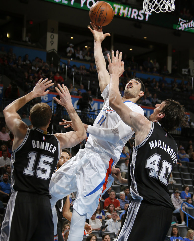 Photo - Oklahoma City's Enes Kanter (11) shoots from between San Antonio's Matt Bonner (15) and Boban Marjanovic (40) during an NBA basketball game between the Oklahoma City Thunder and the San Antonio Spurs at Chesapeake Energy Arena in Oklahoma City, Saturday, March 26, 2016. Oklahoma City won 11-92. Photo by Bryan Terry, The Oklahoman