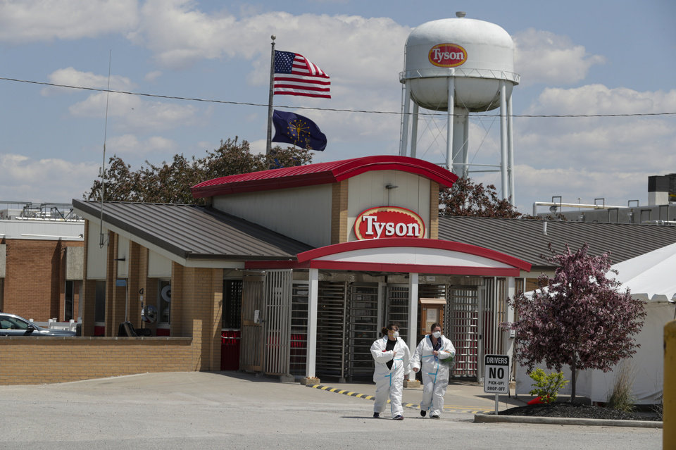 Photo -  Workers leave the Tyson Foods pork processing plant May 7 in Logansport, Ind. [Michael Conroy/Associated Press file photo]