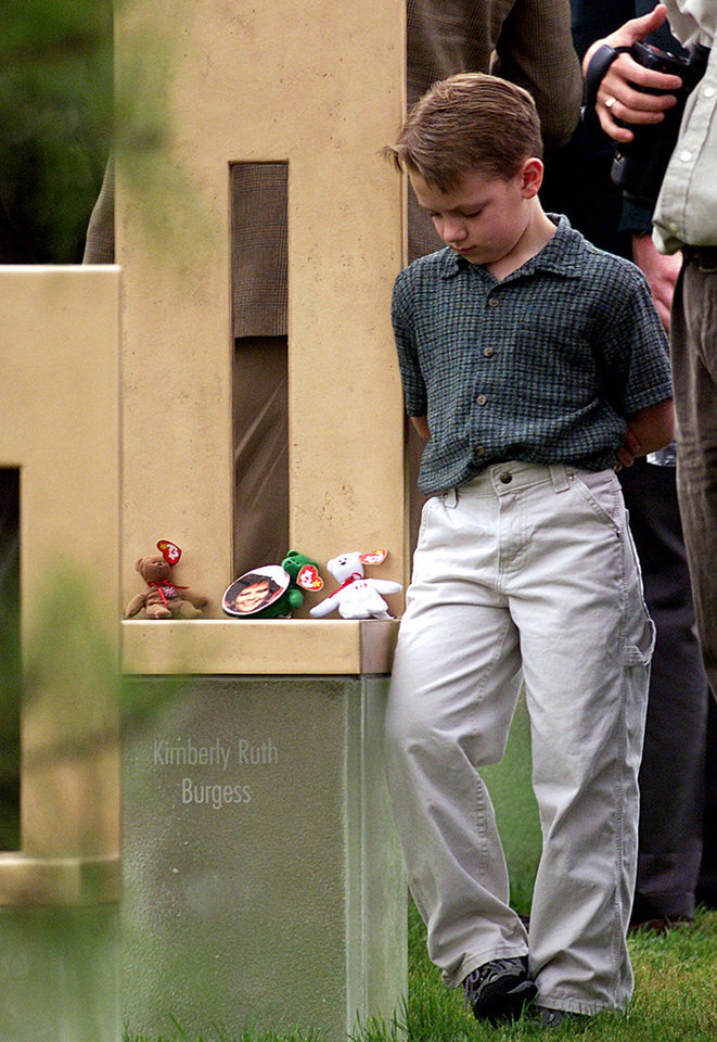 Photo - OKLAHOMA CITY NATIONAL BOMBING MEMORIAL, ALFRED MURRAH FEDERAL BUILDING CAR BOMB EXPLOSION, OPENING, DEDICATION:  An unidentified boy stands next to a chair dedicated to Kimberly Ruth Burgess, one of the 168 chairs for each of the  bombing victims, after the dedication of the Oklahoma City National Memorial, Wednesday, April 19, 2000.  Wednesday is the fifth anniversary of the bombing of the Alfred P. Murrah Federal Building that killed 168 people. (AP Photo/J. Pat Carter)