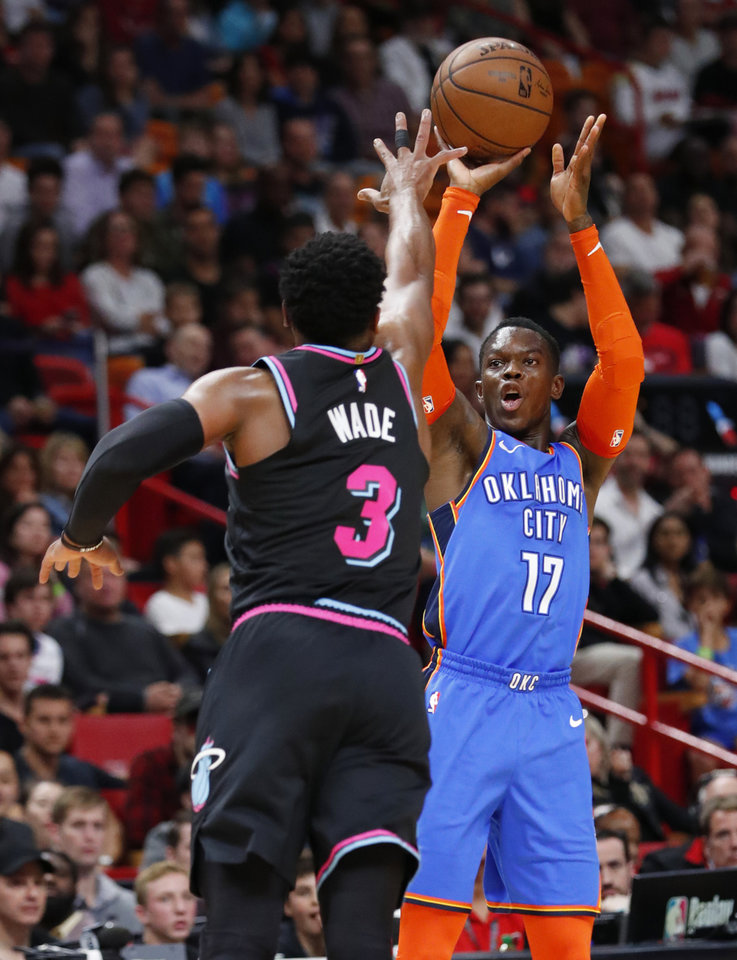 Photo -  Oklahoma City Thunder guard Dennis Schroder shoots a three-point basket against Miami Heat guard Dwyane Wade during Friday's game in Miami. [AP Photo]