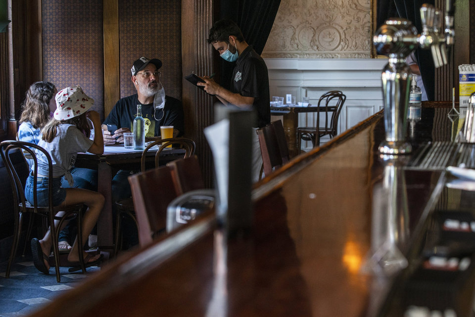 Photo -  A waiter in a face mask takes the order of customers inside a local restaurant during lunch during the coronavirus pandemic on Friday, Sept. 4, 2020, in Hoboken, N.J. (AP Photo/Eduardo Munoz Alvarez)