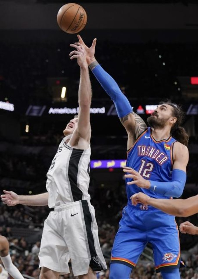 Photo -  Oklahoma City's Steven Adams, right, and San Antonio's Jakob Poeltl fight for possession during Thursday night's game in San Antonio. [AP Photo/Darren Abate]