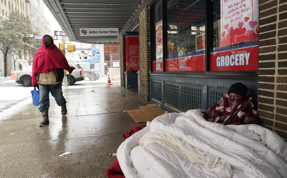 Photo -  FILE - In this Feb. 18, 2021, file photo, a woman living on the streets uses blankets to keep warm in downtown San Antonio. Snow, ice and sub-freezing weather continue to wreak havoc on the state's power grid and utilities. (AP Photo/Eric Gay)