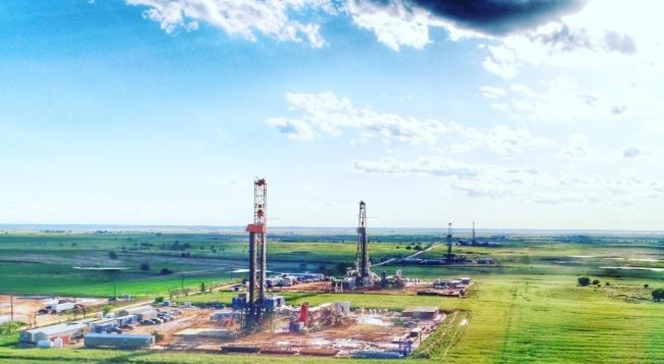 Photo -  Rigs drill wells that are part of an Encana cube development project in the STACK play of the Anadarko Basin. [PROVIDED]