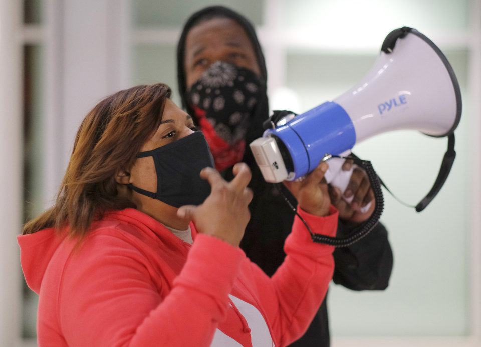 Photo - Jabee Williams holds the megaphone for Cherisse Baker as she speaks, as BLM holds a protest rally at the Oklahoma City Police Headquarters, then marched to the Oklahoma County Courthouse, then finally to the Oklahoma City Municipal Court Building Friday night in response to OCPD officers  shooting and killing a Black man in a northwest Oklahoma City parking lot at Penn and Hefner Friday morning, December 11, 2020. [Doug Hoke/The Oklahoman]