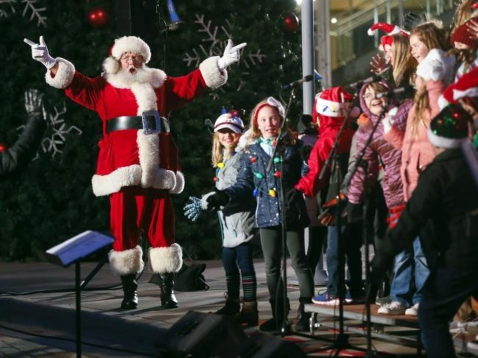 Photo -  Santa Claus sings along with the Edmond Youth Chorus on Monday during the Governor's Christmas Tree Lighting at the Oklahoma History Center in Oklahoma City. [Nate Billings photos/The Oklahoman]
