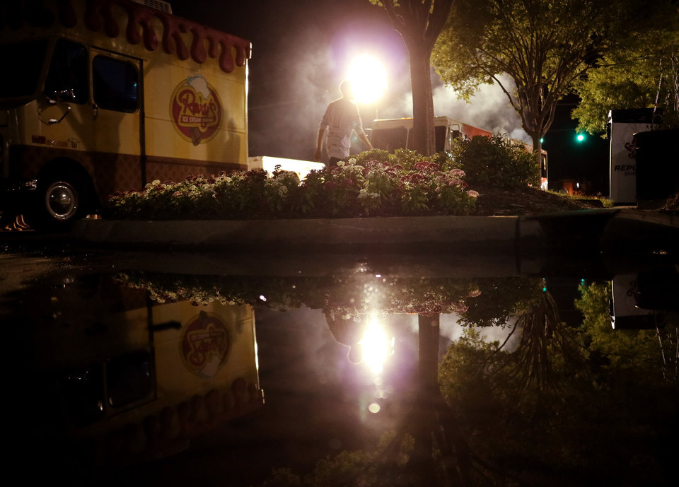 Photo - Lights, people and food trucks are reflected in a water puddle during Heard on Hurd in downtown Edmond Saturday, June 18, 2016. [Photo by Doug Hoke, The Oklahoman]