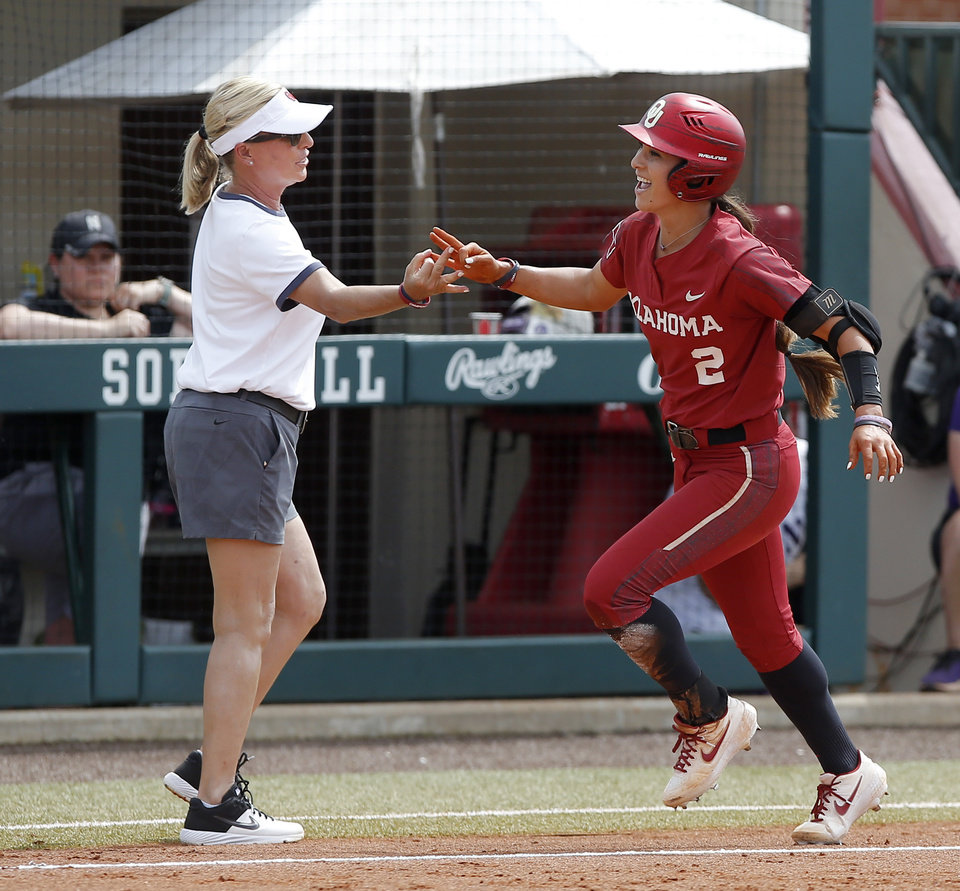 Photo - Oklahoma's Sydney Romero (2) celebrates with coach Patty Gasso after hitting a home run in the third inning of the second softball game in the Norman Super Regional between the University of Oklahoma (OU) and Northwestern in Norman, Okla., Saturday, May 25, 2019. Oklahoma won 8-0 to send them to the Women's College World Series. [Bryan Terry/The Oklahoman]
