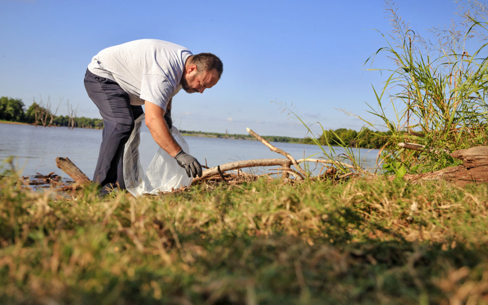 Photo -  Billy Patterson works to fill a bag as he picks up trash at Lake Arcadia's Carl Reherman Park in Edmond on Tuesday. [Photo by Chris Landsberger, The Oklahoman]