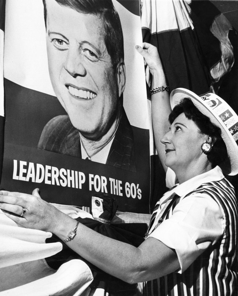 "Photo - STATE, OKLAHOMA, VISITS: 'HANGING DECORATIONS, Mrs. Betty McElroy, 2716 SW 52, is one of many workers preparing for Sen. John (F.) Kennedy's Oklahoma City visit.  She's tacking up the king-sized poster in Municipal Auditorium where the Democratic standard-bearer will appear Thursday night."" Staff photo by Mandell Matheson taken 11/3/60; photo ran in the 11/3/60 Oklahoma City Times."