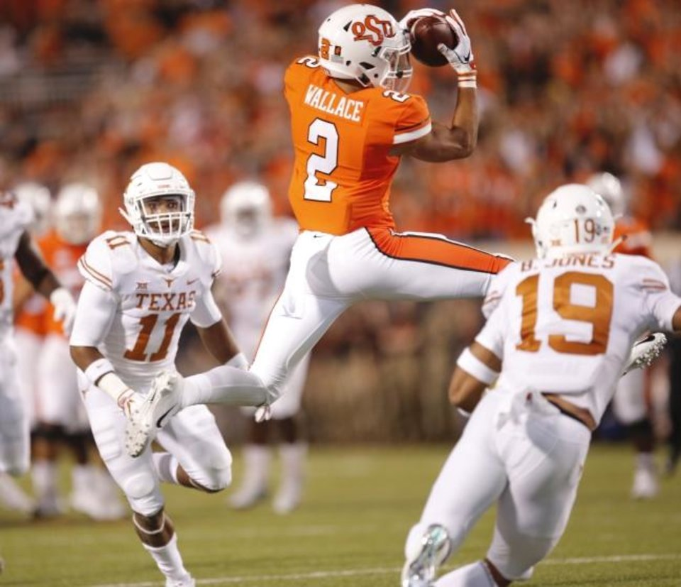 Photo -  Oklahoma State's Tylan Wallace (2) soars for a touchdown reception during last season's upset win against Texas in Stillwater. [Sarah Phipps/The Oklahoman]