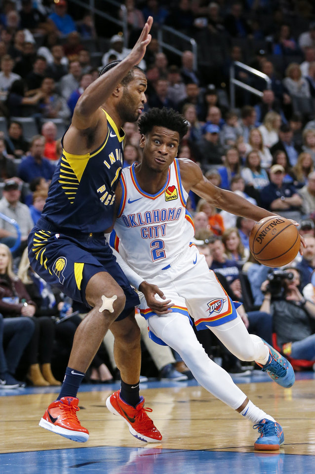 Photo - Oklahoma City's Shai Gilgeous-Alexander (2) drives as Indiana's T.J. Warren (1) defends in the second quarter during an NBA basketball game between the Indiana Pacers and the Oklahoma City Thunder at Chesapeake Energy Arena in Oklahoma City, Wednesday, Dec. 4, 2019. [Nate Billings/The Oklahoman]