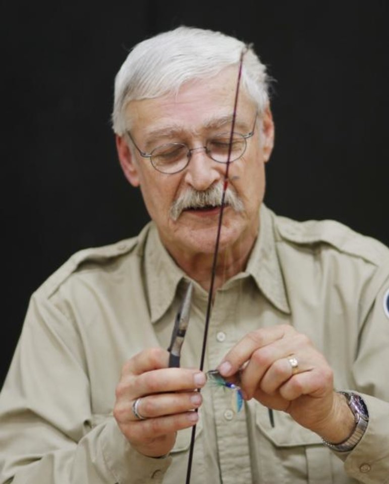 Photo -  Bob Martin demonstrates how to tie on a lure during a fishing clinic last year. Martin, Oklahoma City's fisheries biologist for the past 37 years, retired Jan. 3 but he still plans to volunteer as a fishng instructor. [DOUG HOKE/THE OKLAHOMAN ARCHIVES]