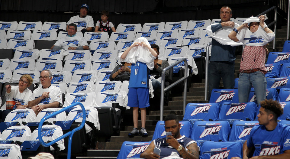 Photo - Thunder fans put on their shirts before Game 3 of the Western Conference finals in the NBA playoffs between the Oklahoma City Thunder and the Golden State Warriors at Chesapeake Energy Arena in Oklahoma City, Sunday, May 22, 2016. Photo by Bryan Terry, The Oklahoman