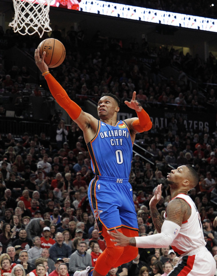 Photo - Oklahoma City Thunder guard Russell Westbrook, left, shoots as Portland Trail Blazers guard Damian Lillard, right, defends during the first half of Game 1 of a first-round NBA basketball playoff series in Portland, Ore., Sunday, April 14, 2019. (AP Photo/Steve Dipaola)