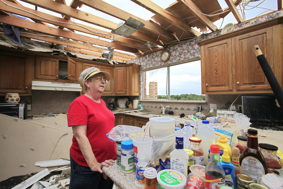 Photo - Tornado aftermath cleanup in Guthrie, Wednesday, May 25, 2011.   Loretta Rice looks over her roofless kitchen in her home that was hit by Tuesdays tornado. Photo by David McDaniel, The Oklahoman