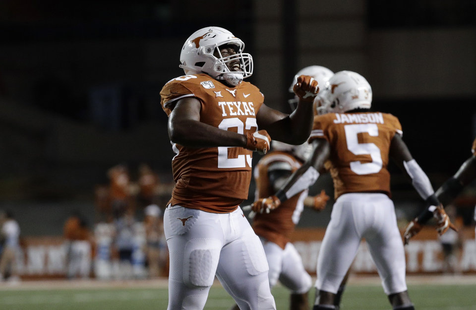Photo - Texas linebacker Jeffrey McCulloch (23) and teammates celebrates a stop against Oklahoma State during the second half of an NCAA college football game Saturday, Sept. 21, 2019, in Austin, Texas. (AP Photo/Eric Gay)