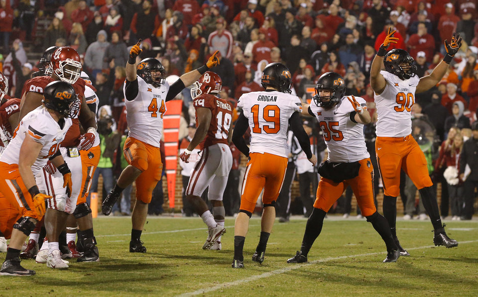 Photo - Oklahoma State's Ben Grogan (19), celebrates with Kip Smith (35), Trace Clark (90), and Jeremy Seaton (44) after kicking the game-winning field goal in overtime of a Bedlam college football game between the University of Oklahoma Sooners (OU) and the Oklahoma State Cowboys (OSU) at Gaylord Family-Oklahoma Memorial Stadium in Norman, Okla., Saturday, Dec. 6, 2014. Photo by Bryan Terry, The Oklahoman