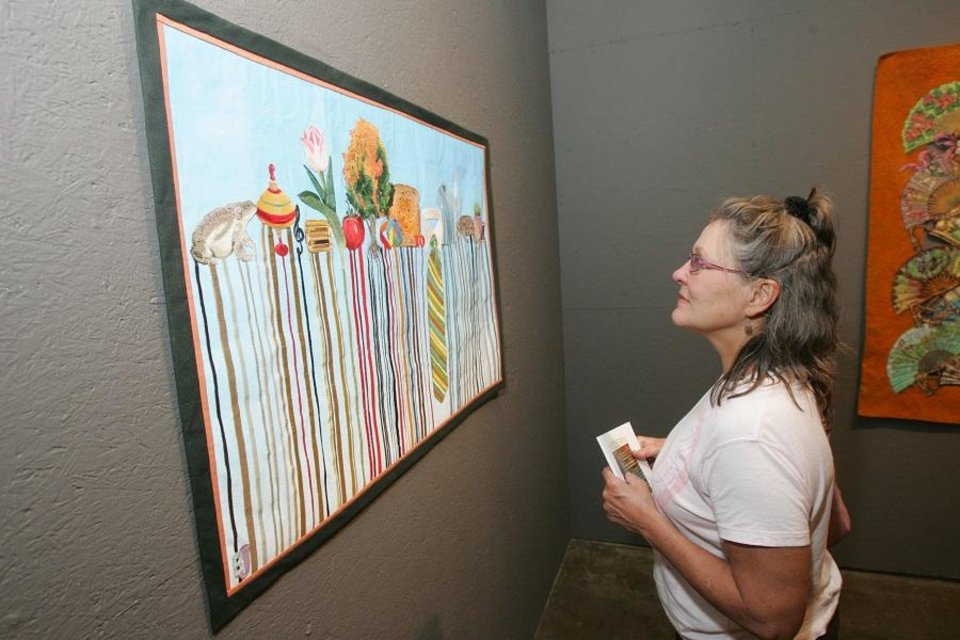 Photo - Cynthia Brown, of Tulsa, looks at work by B.J. Adams at Artspace at Untitled in Oklahoma City, Oklahoma July 31, 2009. [The Oklahoman Archives]