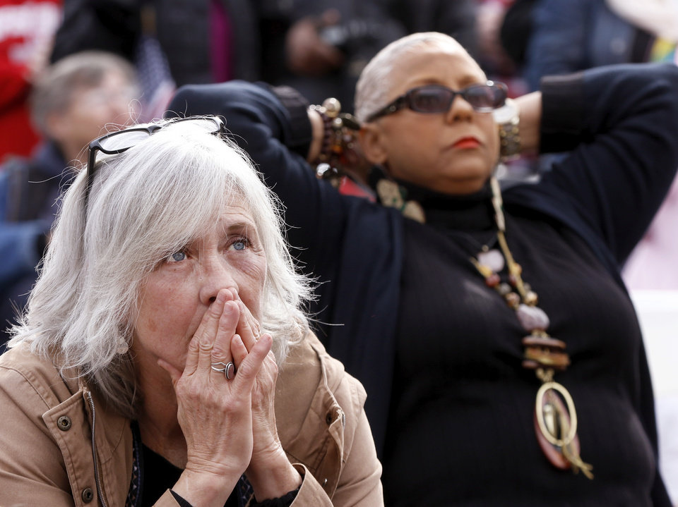 Photo - Two women listen to the words of one of the speakers at the rally. A crowd estimated by organizers to be as many as 7,000 people came to the state Capitol in Oklahoma City Saturday, Jan. 21, 2017, to rally, using their voices and signs to express displeasure with the nation's new administration as part of a larger network of marches taking place across the country following Donald Trump's inauguration.   The Women's March on Oklahoma included a walk along Lincoln Blvd., with the Capitol as a backdrop, and a rally on the Capitol's south plaza that featured nearly a dozen speakers.  Photo by Jim Beckel, The Oklahoman