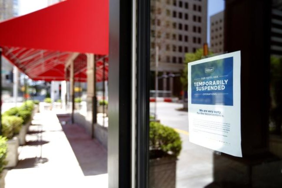 Photo -  A sign about a temporary closure is pictured on the doors of Skirvin Hilton which closed in late March.  [SARAH PHIPPS/THE OKLAHOMAN]