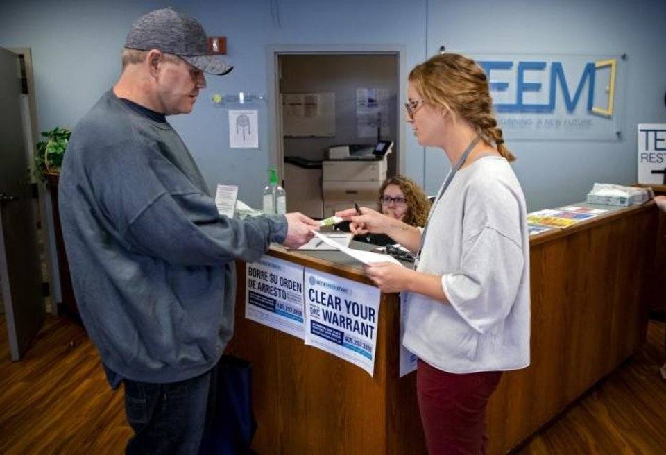 Photo - The Education and Employment Ministry (TEEM) Supervisor of Reentry Abby Otto provides a bus pass to Warren Rawls, who was released from prison through commutation on Monday, while at the TEEM office in Oklahoma City, Okla. on Tuesday, Nov. 5, 2019. TEEM and other area nonprofit groups and community partners are working to help people who were released through Monday's commutation make the transition to life outside of prison.      [Chris Landsberger/The Oklahoman]