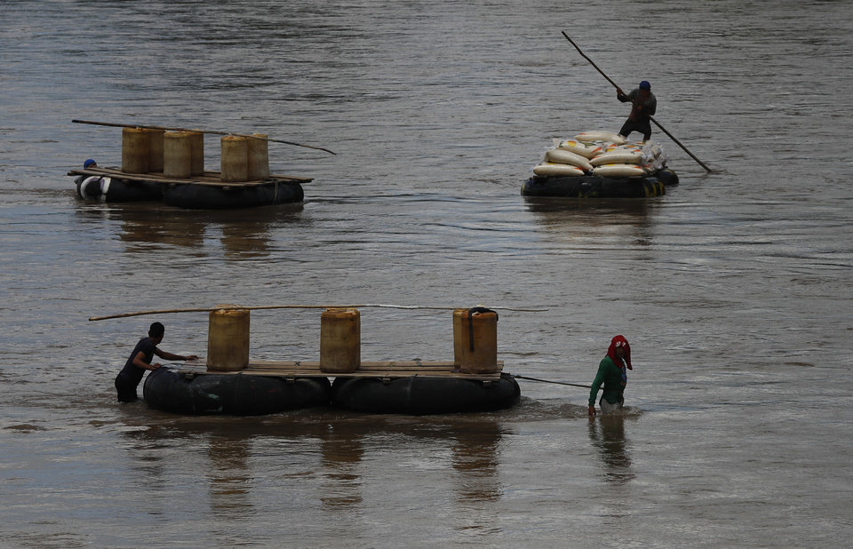 Photo -  Men use rafts to transport black-market gasoline across the Suchiate River from Guatemala to Mexico, as one pushes sacks of corn in the opposite direction to Guatemala, near Ciudad Hidalgo, Mexico, Thursday, June 6, 2019. U.S. President Donald Trump has pledged to impose 5% tariffs on Mexican products unless Mexico country prevents Central American migrants from traveling through its territory. Some migrants pay raft operators in order to avoid swimming or going through the official border crossing. (AP Photo/Marco Ugarte)