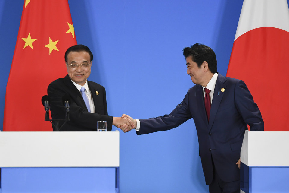 Photo -  China's Premier Li Keqiang, left, shakes hands with Japan's Prime Minister Shinzo Abe at a joint press conference during the 8th trilateral leaders' meeting between China, South Korea and Japan in Chengdu, in southwest China's Sichuan province on Tuesday, Dec. 24, 2019. (Wang Zhao/Pool Photo via AP)