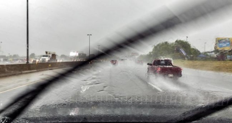 Photo -  Traffic makes its way down I-40 through heavy rains in Oklahoma City on Thursday. [Chris Landsberger/The Oklahoman]