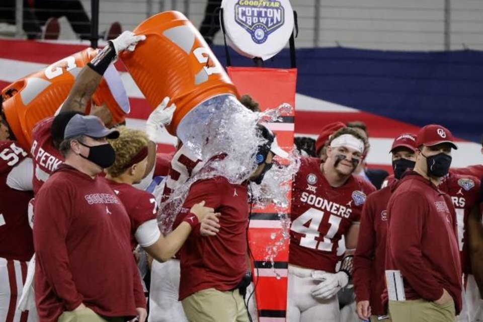 Photo -  Oklahoma defensive end Ronnie Perkins (7) douses coach Lincoln Riley, center, in the closing seconds of the team's Cotton Bowl NCAA college football game against Florida in Arlington, Texas, Wednesday, Dec. 30, 2020. Oklahoma won 55-20. (AP Photo/Michael Ainsworth)